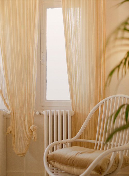 Cream drapes and velvet wicker chair in hotel suite