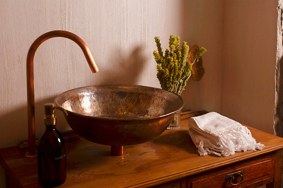 Copper coloured sink and tap on antique console table