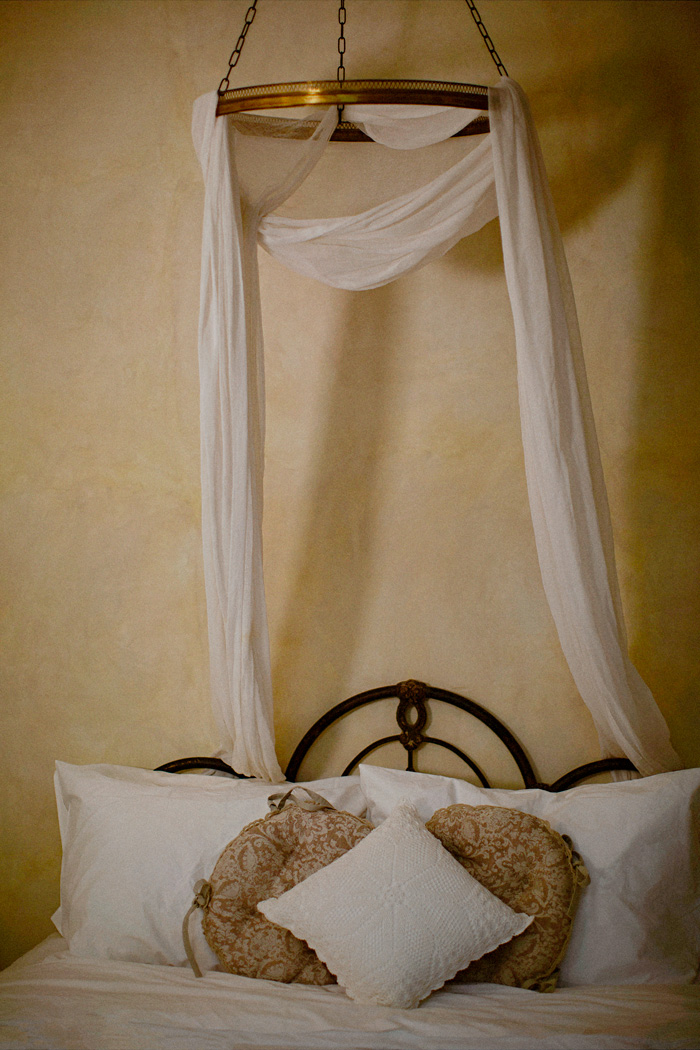 Fabric draped canopy over bed in hotel suite