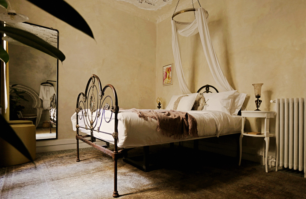 Whimsical drapes over wrought iron bed in hotel suite