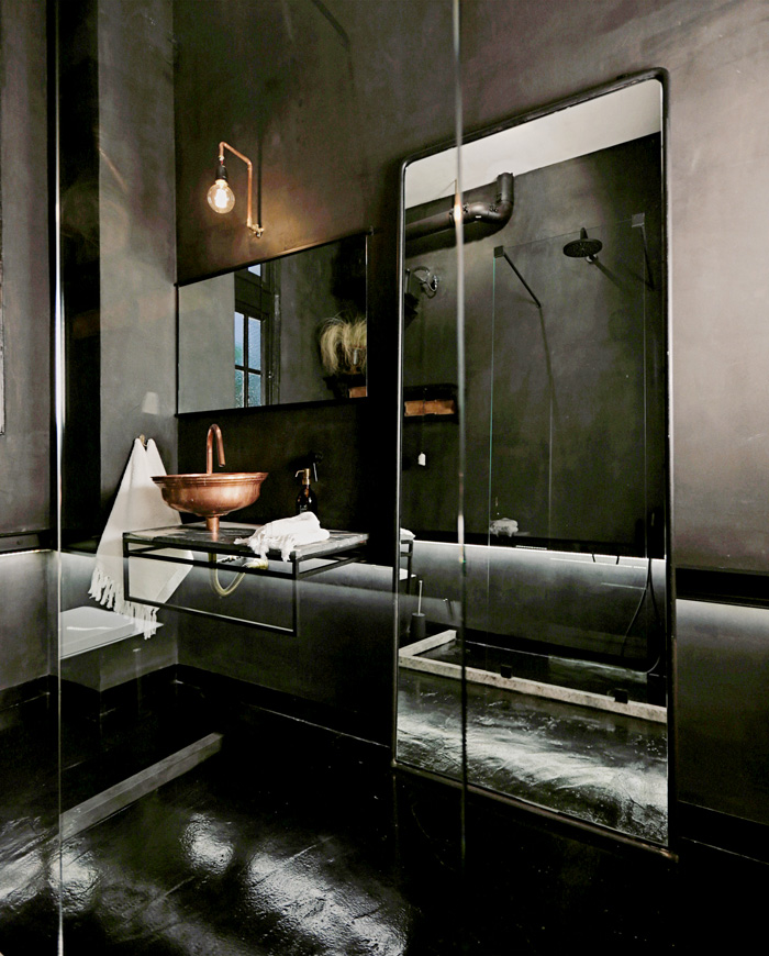 Mirrored bathroom with bronze sink in The Dreamers hotel suite