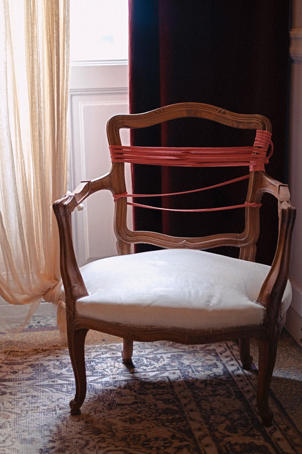 Antique chair wrapped in ribbon in hotel suite