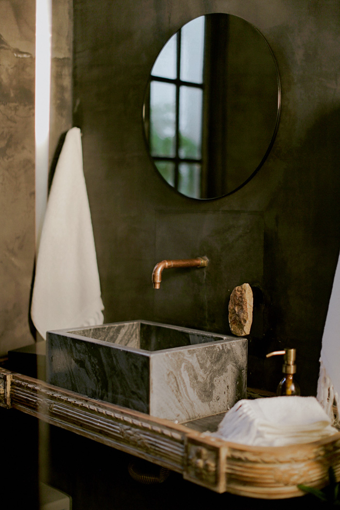 Marble sink and copper tap in hotel bathroom suite